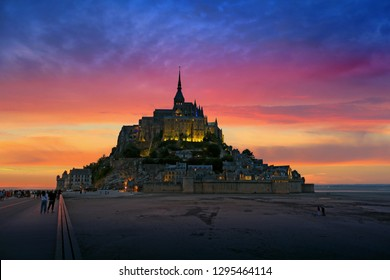 Dark silhouette of Mont-Saint-Michel abbey on orange and pink sunset sky background. Famous landmark of Normandy, France