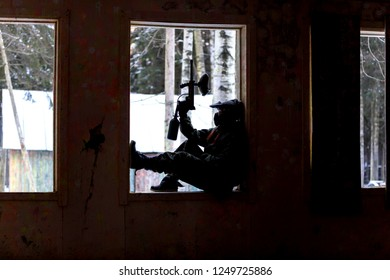 Dark silhouette of paintball player sitting on window sill in abandoned house
