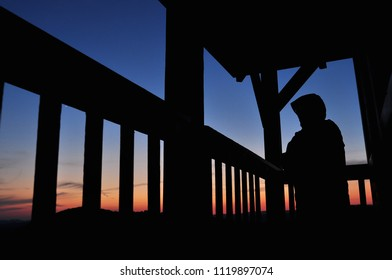 Dark silhouette of an person with blue sky after sunset on wooden balcony