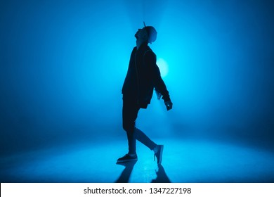 A dark silhouette of a singer on the stage, dancing alone during performance on dark blue neon background with smoke and lights.