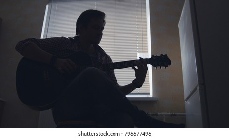 Dark silhouette of young attractive man musician composes music on the guitar and plays, silhouette