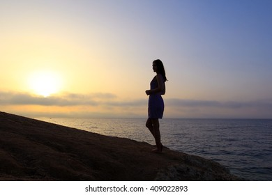 dark silhouette of young slender woman on the beach at sunrise
