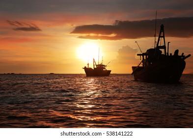 Dark silhouettes of anchored fishing boats in the setting sun. Mui Ne, Vietnam