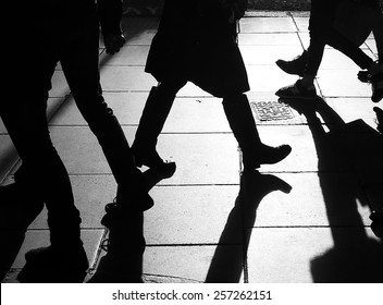 Dark silhouettes of legs walking on the side walk in bright back light