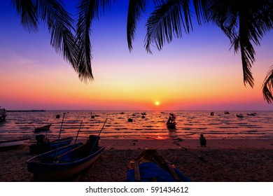 Dark silhouettes of palm trees and amazing cloudy sky on sunset at tropical island in Indian Ocean. Coconut Tree with Beautiful and romantic sunset. Koh Tao popular tourist destination in Thailand.