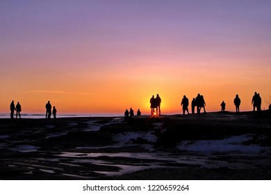 Dark silhouettes of people on a winter sunset background