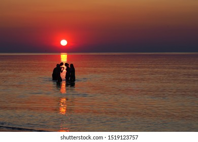 Dark silhouettes of teenagers playing in the sea during sunset. A group of girls and boys having fun in water. A boy is presenting his muscles to the girls.