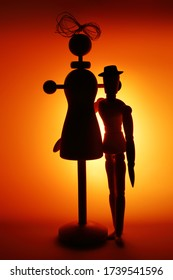 Dark silhouettes of two wooden dolls in the form of a mannequin and gestalts in a contoured orange light. Close up. A funny picture on the topic of love relationships between very different people.
