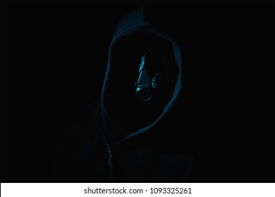 Dark and sinister with a mask on figure in a hood against a black background