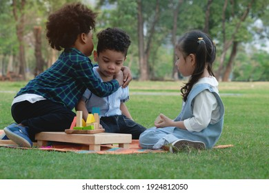 Dark skinned boy hugged and comforted his little friend, group of multi-ethnic kids in park, little girl looked closely, warm relationship between children