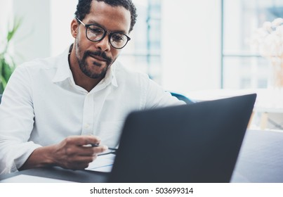 Dark skinned coworker wearing glasses and using laptop in modern office.African american man in white shirt working on workplace.Horizontal,blurred background.