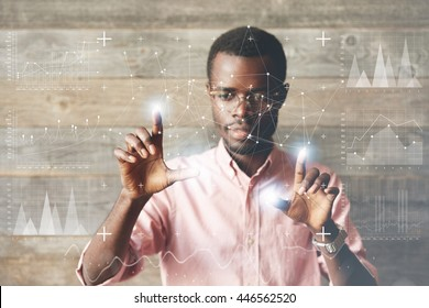 Dark skinned entrepreneur working with virtual screen, navigating and changing positions of icons on futuristic technology display with fingers, looking at the panel absorbedly with excitement