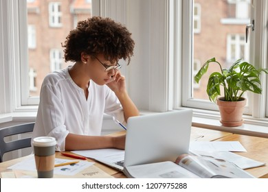 Dark skinned female specialist studies graphs, statistics, has phone conversation with business partner, thinks how raise profits, prepares financial report on laptop computer, poses at workspace
