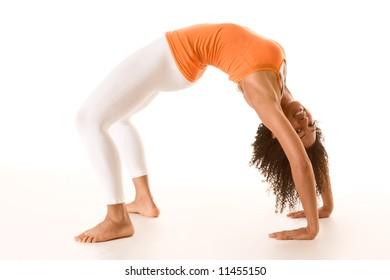Dark skinned fit woman holding bridge stretching pose