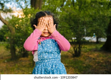 Dark skinned hispanic toddler girl a blue denim sarafan, pink shirt in summer park, holding her hands at her eyes playing hide and seek.
