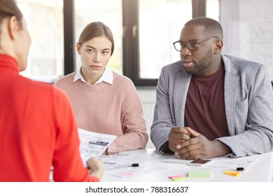 Dark skinned male and females coworkers sit together at working place, discuss opinions and ideas for new startup, plan strategies, have serious looks. Diverse crew of office workers have meeting