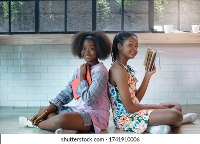 Dark skinned teens studying books on the floor, looking at camera