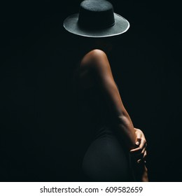 dark skinned woman on a black background with a fashionable hat on his head