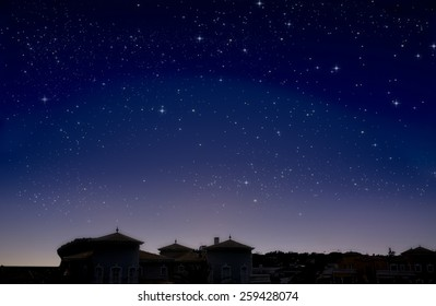 A dark sky with white shining stars, twilight from far horizon line, buildings are black with lighting outlines