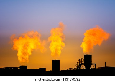 Dark smoke comming from the chimneys of an old factory.
