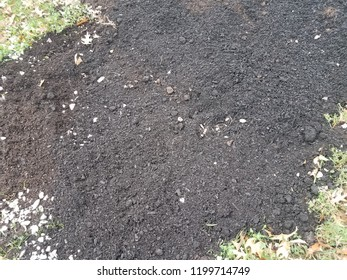 dark soil and with mulch and green lawn and rocks