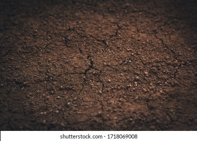 Dark soil texture closeup of dry soil background