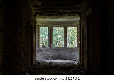 Dark, spooky tunnel, corridor with large windows at the end in abandoned sludge treatment sanatorium, Baldone city, Latvia