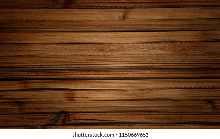 Dark stained brown reclaimed wood surface with aged boards lined up. Wooden planks on a wall or floor with grain and texture. Neutral stained vintage wood background.