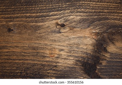 Dark stained wood abstract background, backdrop.  Textured with knots and grain. Graphic resource.