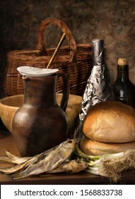 dark still life with a basket, a loaf of bread, dried fish, green onions, a clay jug, a bottle on a brown background