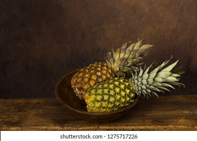 Dark still life with fresh pineapples on an antique wooden table