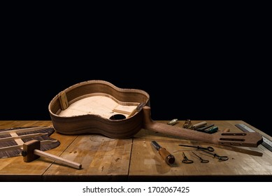 Dark still life of luthier workbench, guitar build. Spanish classic. Guitar in unfinished construction with tools. dark black background.