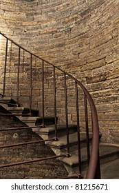 Dark stone spiral staircase with railings