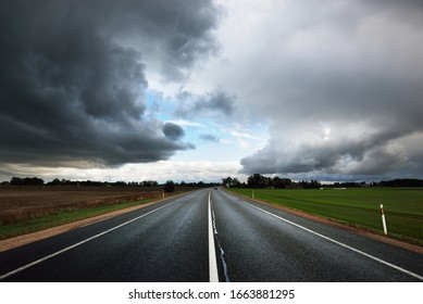 Dark storm clouds above the empty highway through the agricultural fields. Dramatic evening sky. Latvia