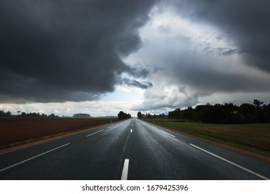 Dark storm clouds above the empty highway through the agricultural fields. Dramatic evening sky after the rain. Latvia