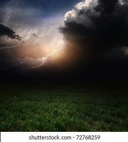 Dark storm clouds with flashes over meadow with green grass