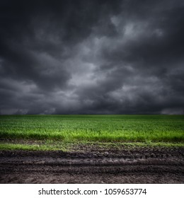 Dark storm clouds over green field and dirt road