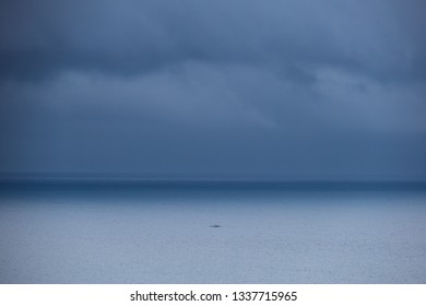 Dark storm clouds and tiny boat on a tropical sea - Diapila Beach, Palawan - Philippines