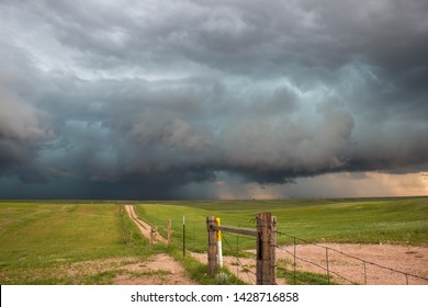 A dark storm looms on the horizon at the end of a dirt road in the countryside.