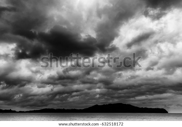 Dark stormy clouds ferociously swarm over the island in the sea.