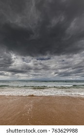 dark stormy clouds over a calm ocean with waves and  water washing ashore