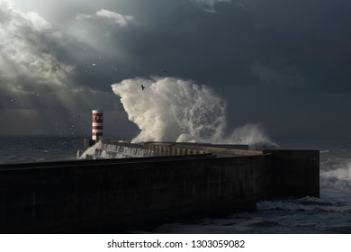 Dark stormy day in the Douro river mouth with sunbeams and big sea wave splash over pier and beacon, Porto, Portugal.