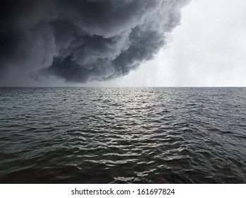 Dark stormy rain cloud in the horizon of a wavy sea.