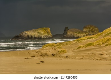 Dark stormy sky above Bird Rocks at the north end of Cannon Beach, Oregon with ocean surf, sandy beach, sand dune, and dune grass.