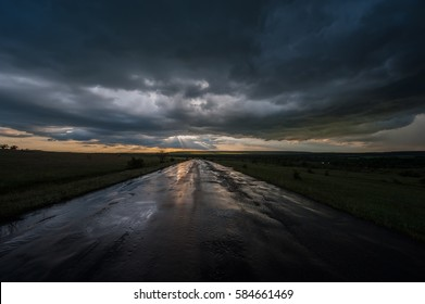 dark stormy sky and clouds and a wet road in the rain