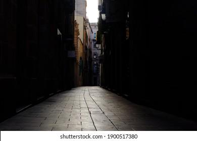 A dark street between high buildings