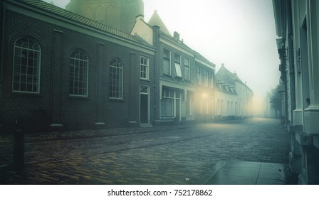 A dark street with fog and mist early in the morning lit by weak streetlights