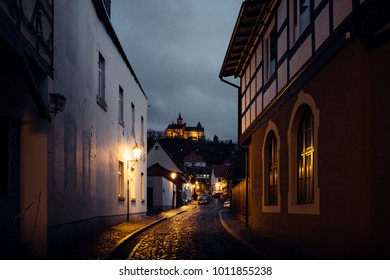 Dark street with view to the castle Wernigerode, at night with lighting
