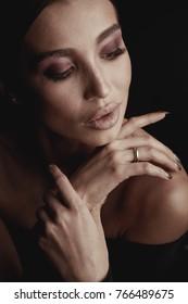 Dark studio portrait of elegant and sexy brunette woman with brown eyes and beautiful hands