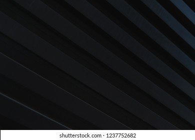 Dark stylish abstract background of wooden boards painted in black color. Natural background. Soft focus and shallow depth of field.